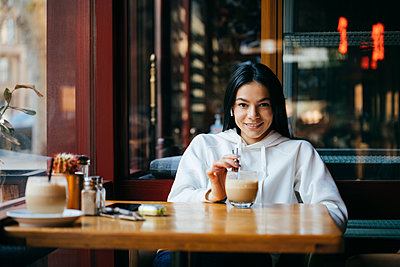 Happy woman having coffee at cafeteria - p300m2282464 by alev