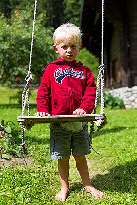 Little boy standing at swing - p756m1464829 by Bénédicte Lassalle