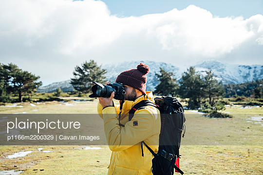 Young man with yellow jacket and backpack taking pictures on the mount - p1166m2200329 by Cavan Images