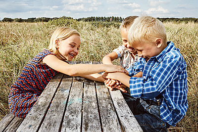 Three children playing on a small wooden table in a meadow - p1540m2200506 by Marie Tercafs