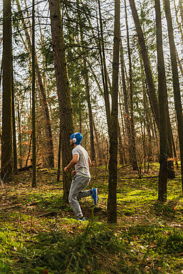 Young man jogging on forest path - p300m1188688 by Uwe Umstätter