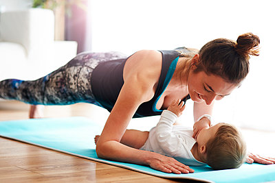 Mother with baby exercising on yoga mat at home - p300m1580968 von gpointstudio