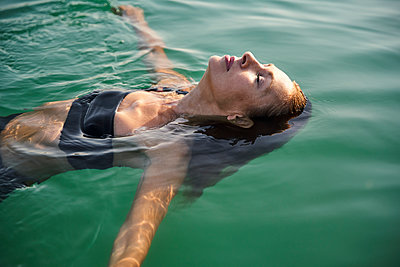 Mature woman floating in a lake with closed eyes - p300m2140950 by Philipp Nemenz