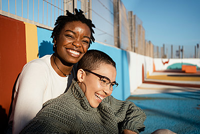 Female friends smiling while sitting at sports court - p300m2243342 by Rafa Cortés