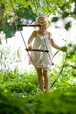 Girl playing in garden with swing and hose - p31226041 by Ulf Huett Nilsson