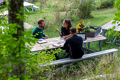 Woman and men at picnic bench - p312m2217148 by Christian Ferm