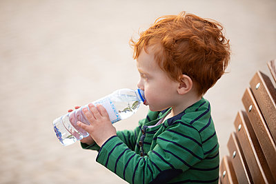 Boy drinking water on park bench - p429m2091461 by Gonçalo Barriga