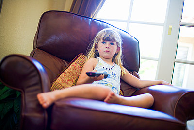 Caucasian girl sitting in armchair holding remote control - p555m1304450 by Jed Share/Kaoru Share