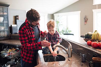 Father watching son wash hands in kitchen sink - p924m2074158 by Viara Mileva