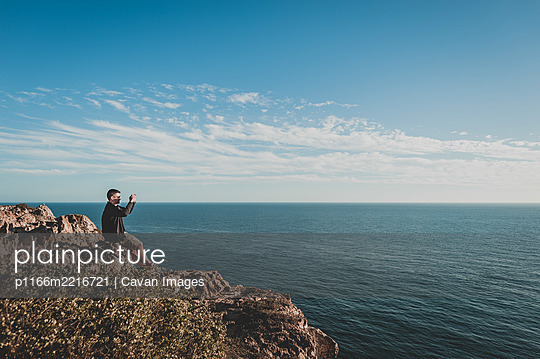 Young man taking photo of ocean from cliff in Sagres, Portugal - p1166m2216721 by Cavan Images
