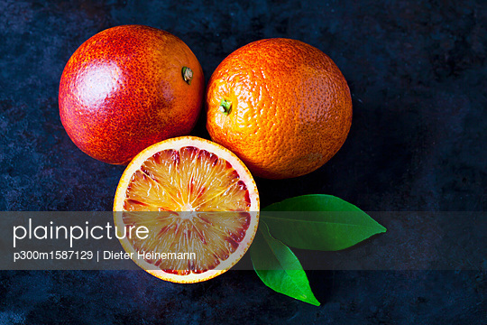Two whole and a half blood orange on dark ground - p300m1587129 von Dieter Heinemann
