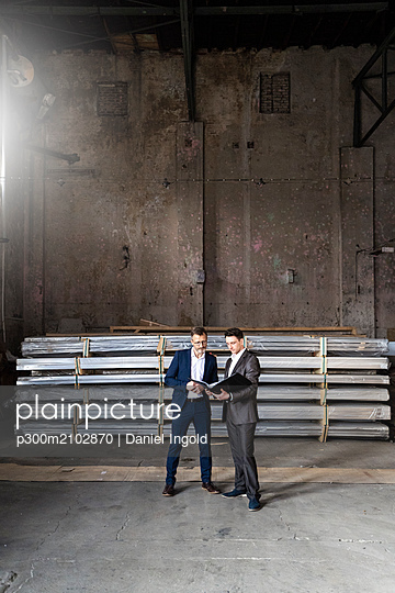 Two businessmen with folder talking in an old storehouse - p300m2102870 by Daniel Ingold
