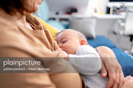 Mother breastfeeding her son at home - p300m2264622 by Albert Martínez