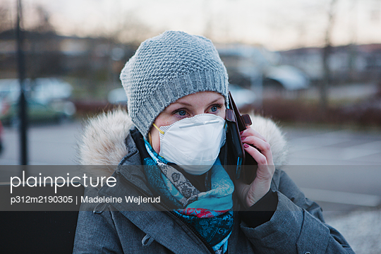 Woman wearing protective mask talking via cell phone - p312m2190305 by Madeleine Wejlerud
