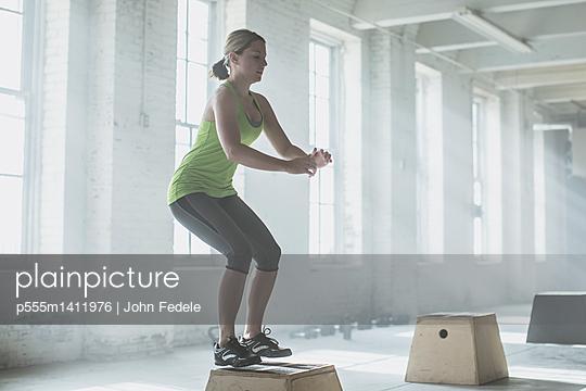 Athlete jumping on platform in gym - p555m1411976 by John Fedele