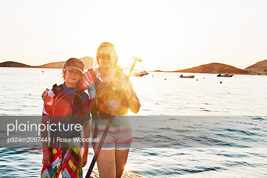 Mother and son standup paddleboarders at sea, portrait, Limnos, Khios, Greece - p924m2097441 by Ross Woodhall