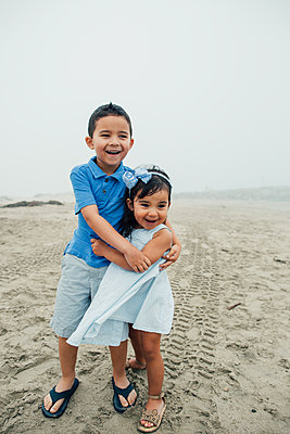 Young Siblings Embrace At Foggy Beach While Smiling Candidly - p1166m2073807 by Cavan Images