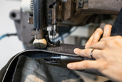 Cropped image of fashion designer sewing jeans in factory - p1185m994367f by Astrakan