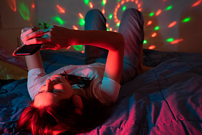Bedroom. Young woman listening to music in bedroom with colorful lights. Neon, music, chill, enjoy, party at home, home alone, music, dance - p300m2250146 von VITTA GALLERY