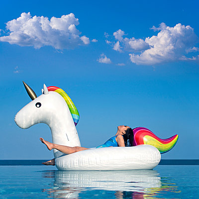 Woman Relaxing on Inflatable Rainbow Unicorn in Swimming Pool - p694m1586784 by Maciej Toporowicz photography