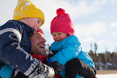 Father holding young sons, smiling, in winter setting - p924m1422671 by Tiina & Geir