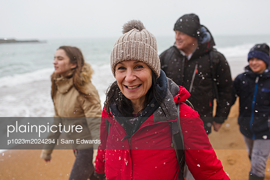 Portrait smiling woman in warm clothing with family on snowy winter ocean beach - p1023m2024294 by Sam Edwards