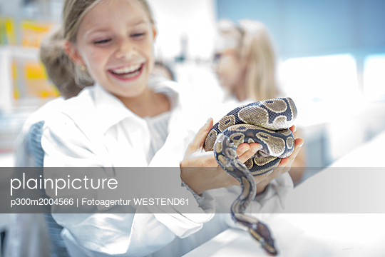 Happy schoolgirl in science class holding snake - p300m2004566 von Fotoagentur WESTEND61