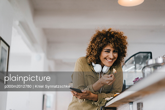 Young woman with headphones in coworking space, taking a break, eating cake - p300m2012780 von Kniel Synnatzschke
