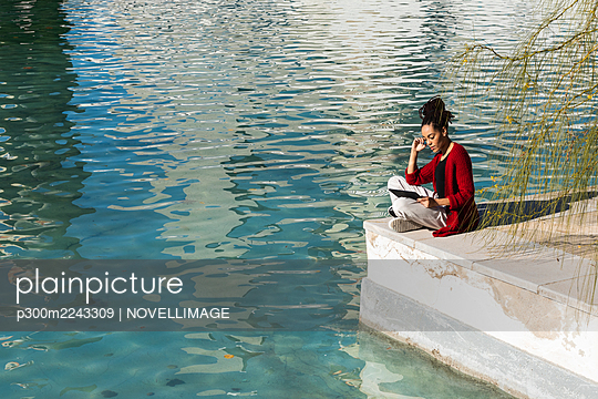 Young woman using digital tablet while sitting cross-legged at edge of promenade over river on sunny day - p300m2243309 by NOVELLIMAGE