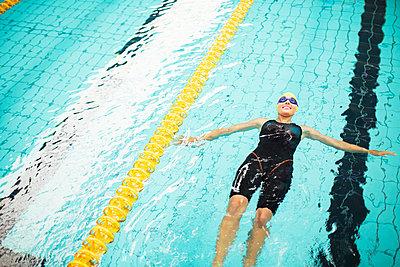 Swimmer floating in pool - p1023m923658f by Paul Bradbury