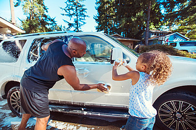 Father and daughter washing car in driveway - p1166m1225977 by Cavan Images