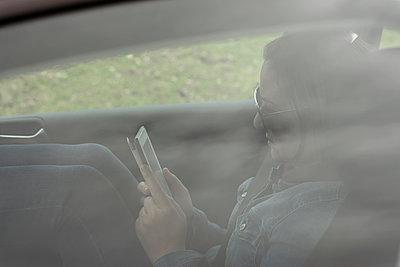 Frau sitzt im Auto und liest in einem E-Book - p1383m2020747 von Wolfgang Steiner