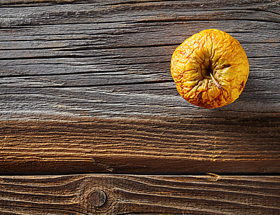 Shrivelled apple on rough wood - p300m1081374f by Dieter Schewig
