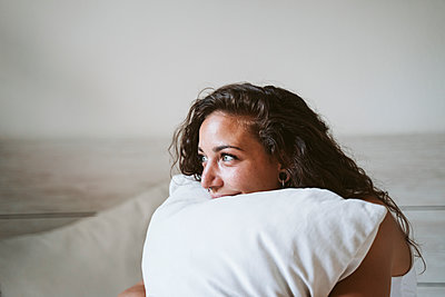 Close-up of thoughtful young woman holding pillow against wall at home - p300m2206614 by Eva Blanco