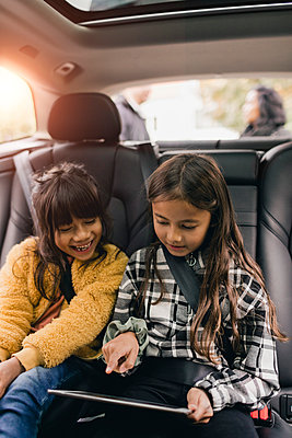 Sisters using digital tablet while sitting in car - p426m2195227 by Maskot