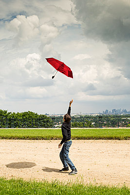 Teenager playing with an umbrella - p445m1153163 by Marie Docher