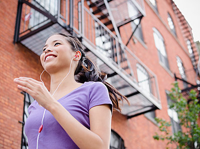 Asian woman jogging and listening to music - p555m1479062 by JGI/Jamie Grill