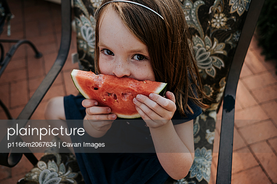 High angle portrait of cute girl eating watermelon while sitting on chair in yard - p1166m2067634 by Cavan Images