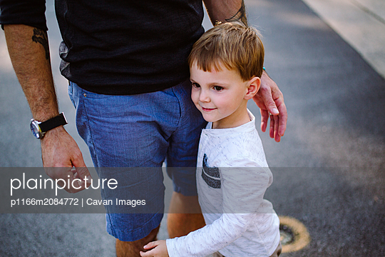 Portrait of a small boy holding on to his father's leg - p1166m2084772 by Cavan Images
