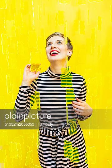 Frau vor einem gelben Hintergrund - p1332m2055053 von Tamboly