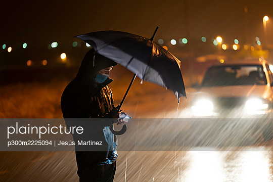 Young man with umbrella and face mask using mobile phone while standing against breakdown car during rainfall - p300m2225094 by Jesús Martinez