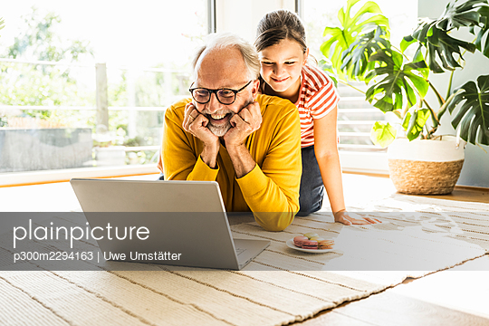 Smiling grandfather with hand on chin using laptop with granddaughter at home - p300m2294163 by Uwe Umstätter