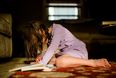 A small child sits on rug in morning light with pile of books reading - p1166m2130195 by Cavan Images