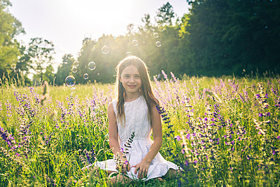 Portrait of smiling girl crouching on flower meadow at evening twilight - p300m1587893 von Sandra Roesch