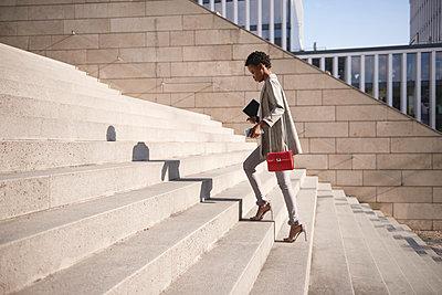 Businesswoman walking up stairs - p300m2004516 by gpointstudio