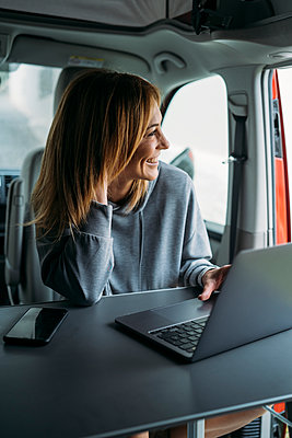 Female freelancer looking away while sitting with laptop and smart phone in van - p300m2276038 by Manu Padilla Photo