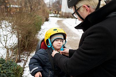 Sweden, Sodermanland, Stockholm, Woman fixing helmet on daughter´s (2-3) head - p352m1186935 by Julia Sjöberg