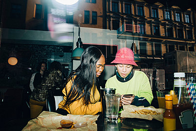 Man showing smart phone to smiling woman seen through transparent glass window - p426m2194730 by Maskot