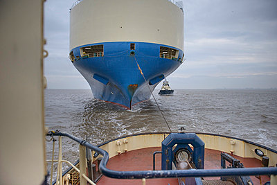 Tugboat pulling ship to harbor - p429m747081f by Monty Rakusen
