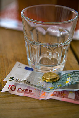 Empty glass and Euro notes and coins - p555m1480207 by Tom Paiva Photography